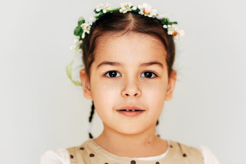 Cierre encima del peinado adorable de la niña del retrato con las flores, sonriendo brightfully, mirando a la cámara con la expre fotografía de archivo