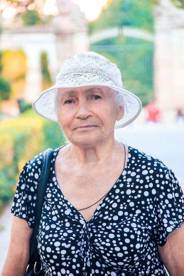 Cierre encima del retrato de una más vieja mujer que se coloca afuera en verano imagen de archivo