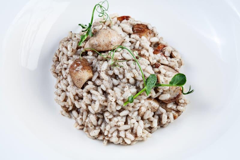 Cierre encima del risotto con las setas del porcini y las pastas de la trufa en el cuenco blanco Cocina italiana hecha en casa Co imagen de archivo libre de regalías