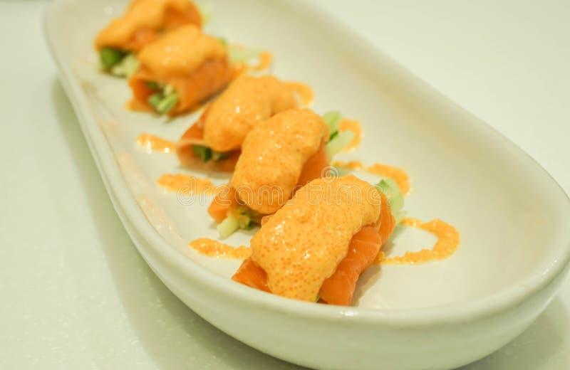 Cierre encima del rollo de color salmón preferido del espárrago con la salsa picante fotografía de archivo