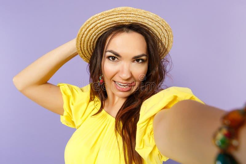 Cierre encima del selfie tirado de mujer joven alegre en el vestido amarillo, lengua de la demostración del sombrero del verano a imagen de archivo libre de regalías