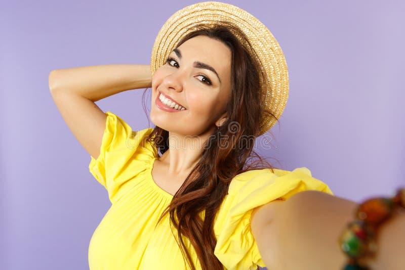 Cierre encima del selfie tirado de mujer joven encantadora en el vestido amarillo, sombrero del verano que pone la mano en la cab foto de archivo libre de regalías