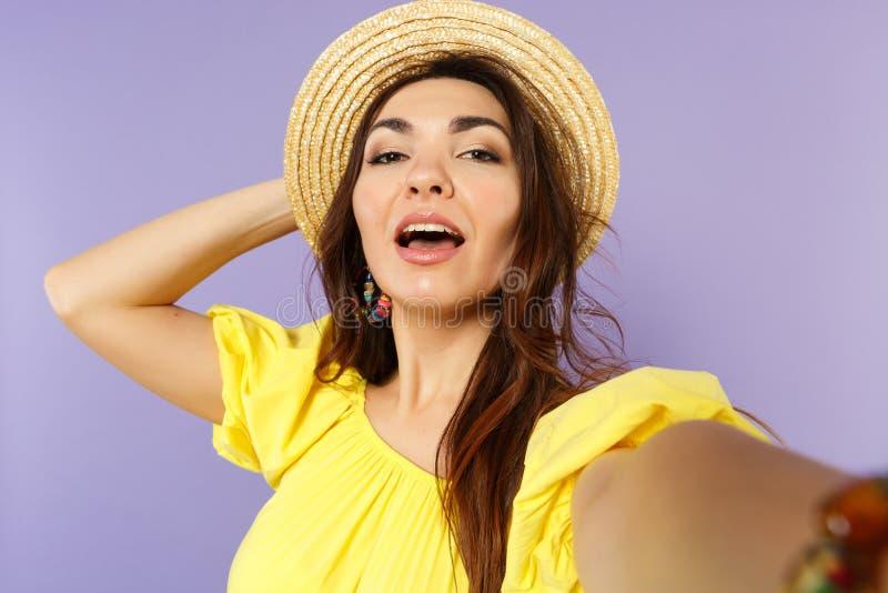 Cierre encima del selfie tirado de mujer joven imponente en el vestido amarillo, sombrero del verano que pone la mano en la cabez fotos de archivo libres de regalías