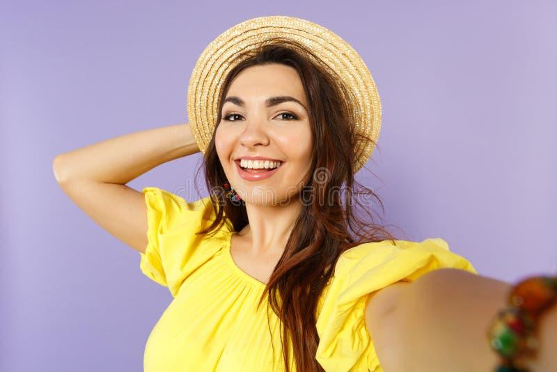 Cierre encima del selfie tirado de mujer joven sonriente en el vestido amarillo, sombrero del verano que pone la mano en la cabez fotos de archivo
