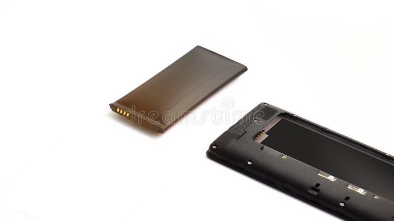 Cierre encima del smartphone hinchado de la batería de ión de litio aislado en el fondo blanco Batería deteriorada lista para que fotos de archivo