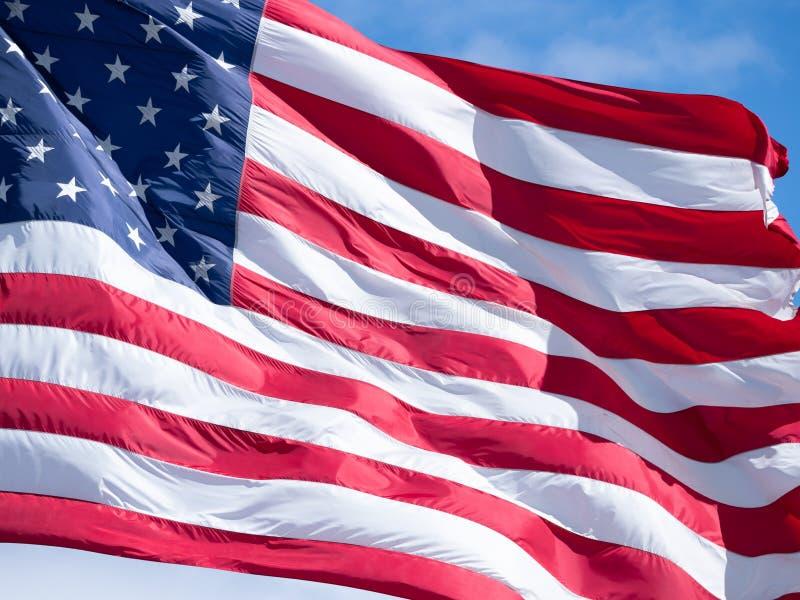 Cierre extremo para arriba de una bandera americana con el cielo azul y las nubes finas en fondo foto de archivo libre de regalías