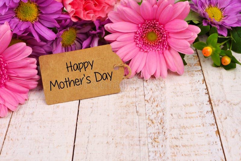 Cierre feliz de la etiqueta del día de madres para arriba con las flores sobre la madera blanca foto de archivo libre de regalías