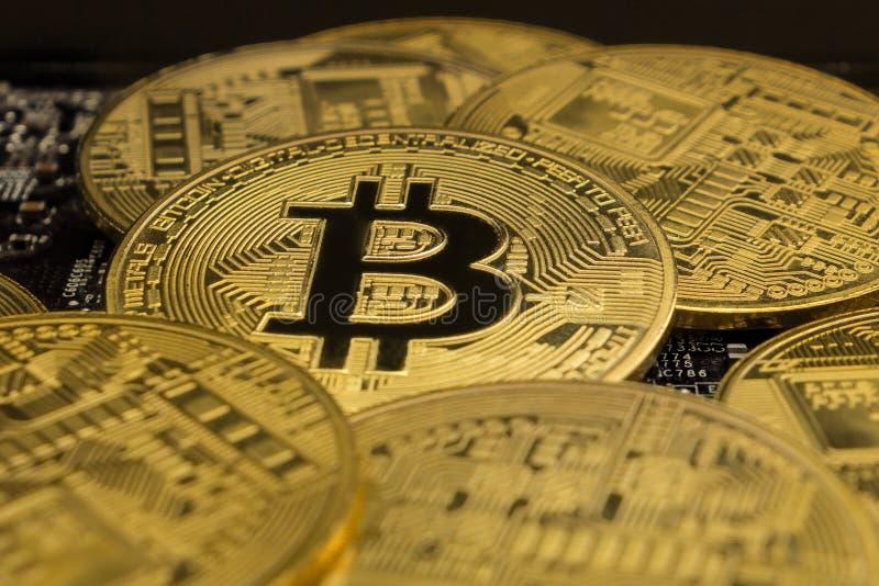 Cierre hasta el metal físico Bitcoins de oro en la placa madre Oro Crypto BTC de la moneda en el microchip de GPU foto de archivo libre de regalías