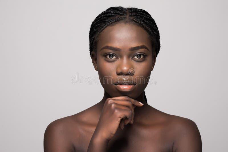 Cierre hermoso de la cara de la mujer africana sana de la piel para arriba aislado sobre fondo gris fotografía de archivo libre de regalías