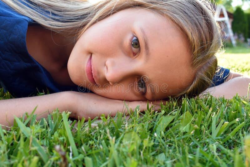 Cierre hermoso de la chica joven para arriba en hierba verde en verano imagenes de archivo