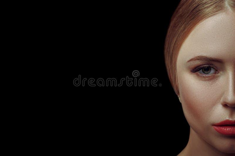 Cierre hermoso del retrato del pelo rubio de la mujer encima del estudio en mitad-cara negra foto de archivo libre de regalías