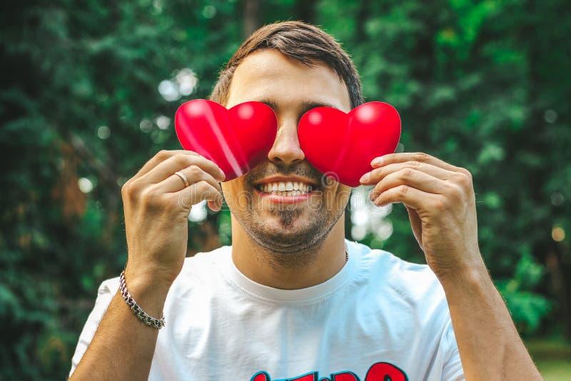 Cierre hermoso joven del hombre encima de los controles los corazones rojos en sus manos en lugar de otro los ojos imágenes de archivo libres de regalías