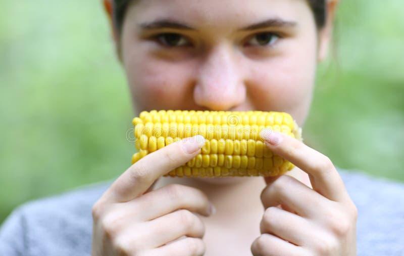 Cierre hervido consumición de la mazorca de maíz de la muchacha del adolescente encima de la foto imagen de archivo