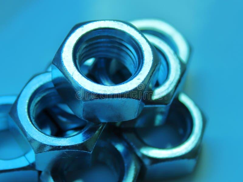 Cierre industrial de la abstracci?n de las nueces encima del fondo azul borroso imagen de archivo