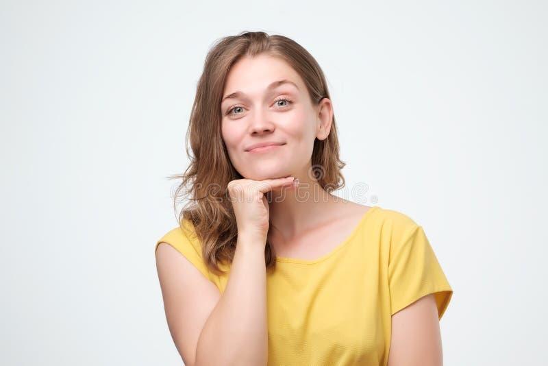 Cierre interior encima del tiro de la mujer europea atractiva joven, sonriendo con gusto y amistoso mientras que escucha usted imagen de archivo
