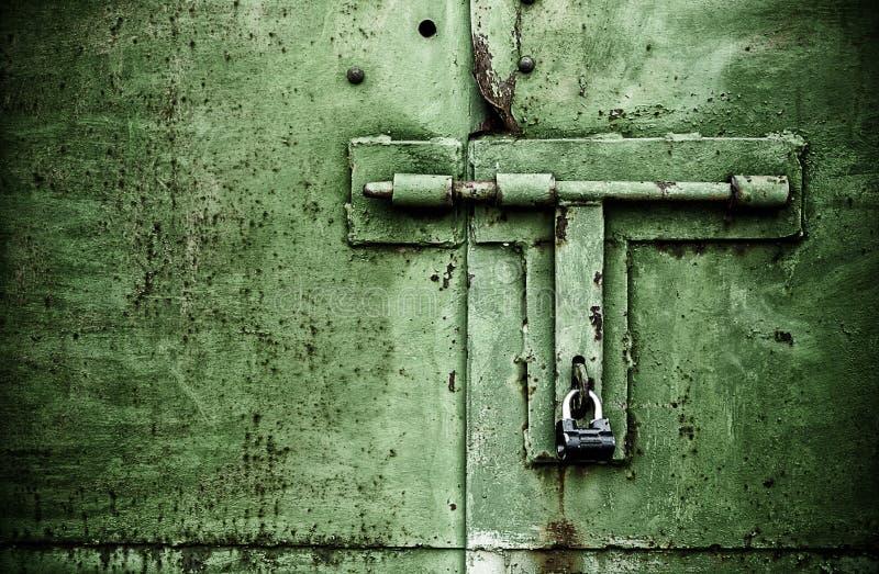 Cierre oxidado de la puerta del color verde encima del detalle con el candado y el perno imagenes de archivo