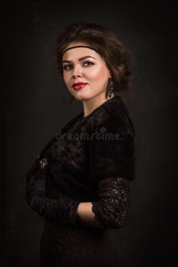 Cierre para arriba Años 20 del rugido Retrato de la mujer en el estilo de Gatsby Mirada de la cámara Mujer joven hermosa en un ve imagenes de archivo