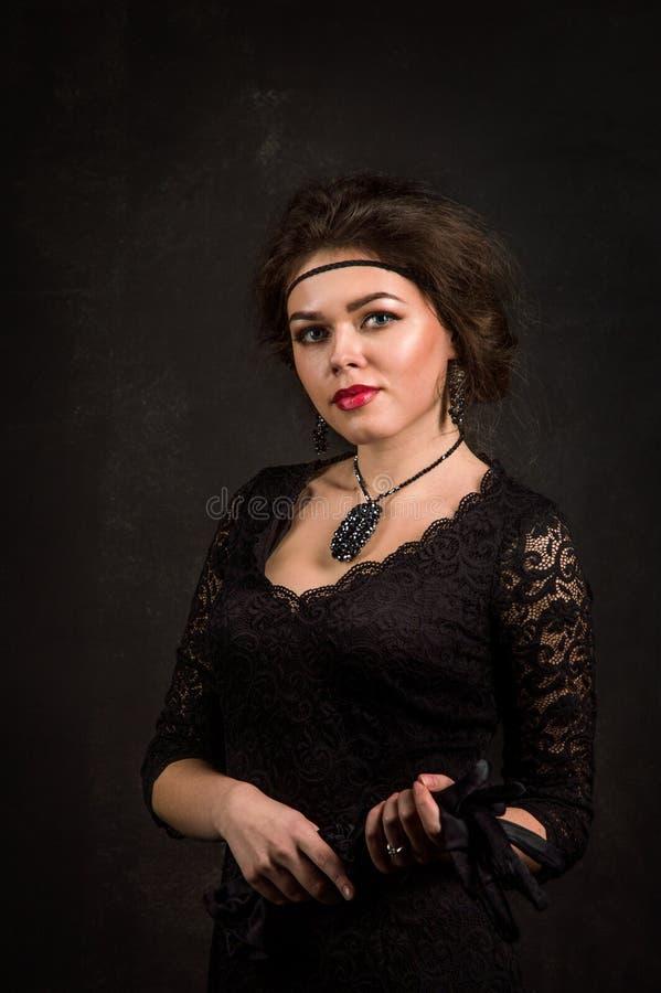 Cierre para arriba Años 20 del rugido Retrato de la mujer en el estilo de Gatsby Mirada de la cámara Una mujer joven hermosa en u imagen de archivo libre de regalías