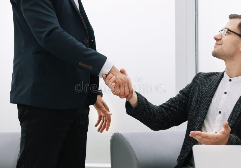 Cierre para arriba Apretón de manos de socios comerciales en un fondo ligero foto de archivo libre de regalías