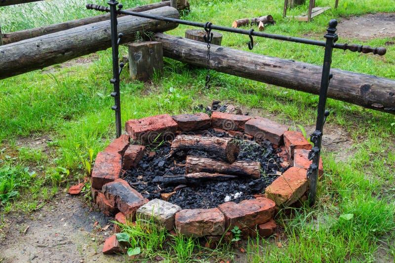Cierre para arriba Chimenea de piedra para cocinar al aire libre Dentro de la leña y de los carbones quemados foto de archivo libre de regalías