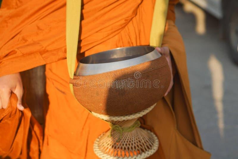 Cierre para arriba: Dé la comida del arroz en limosnas a un monje budista fotos de archivo