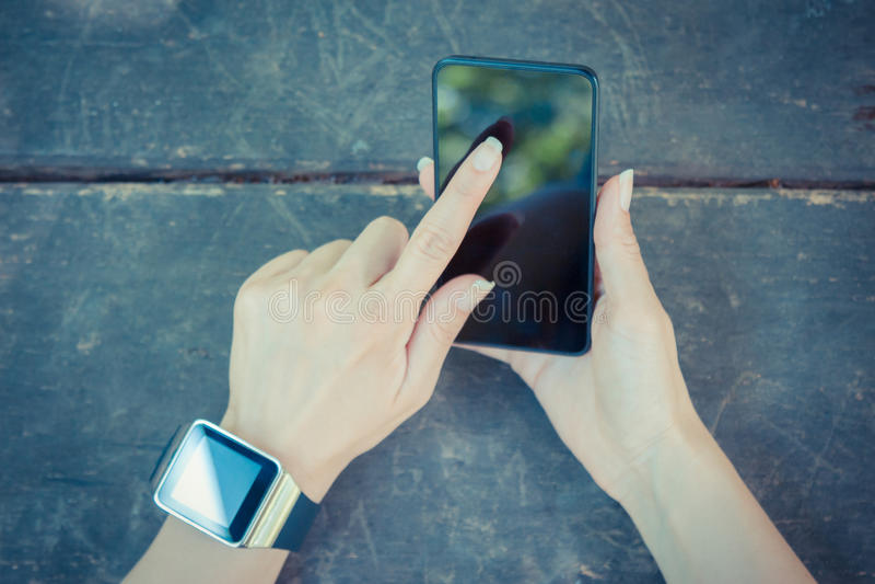 Cierre para arriba de la mano femenina que sostiene el teléfono elegante y que lleva el reloj foto de archivo libre de regalías