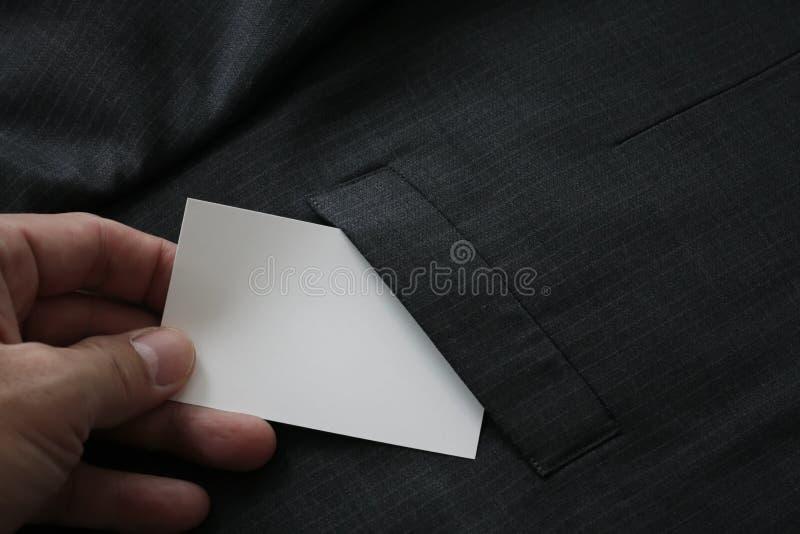 cierre para arriba de la mano que escoge la tarjeta de visita en blanco del hoyo gris del traje imagen de archivo libre de regalías