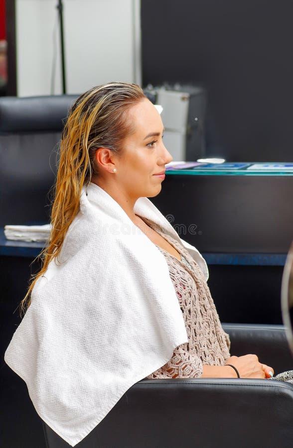 Cierre para arriba de la mujer joven feliz que se sienta en una silla después de un lavado del pelo en el salón de pelo imagen de archivo libre de regalías