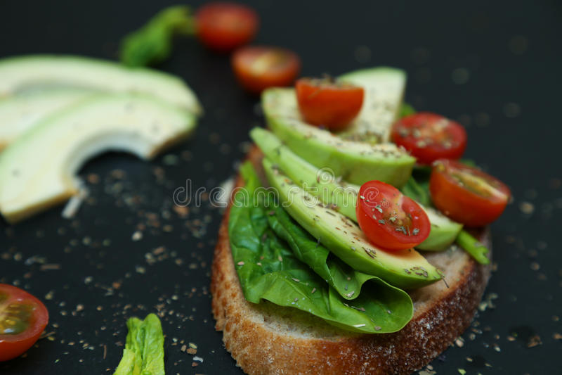 Cierre para arriba de la tostada con las hojas, el aguacate y los tomaties de la espinaca foto de archivo