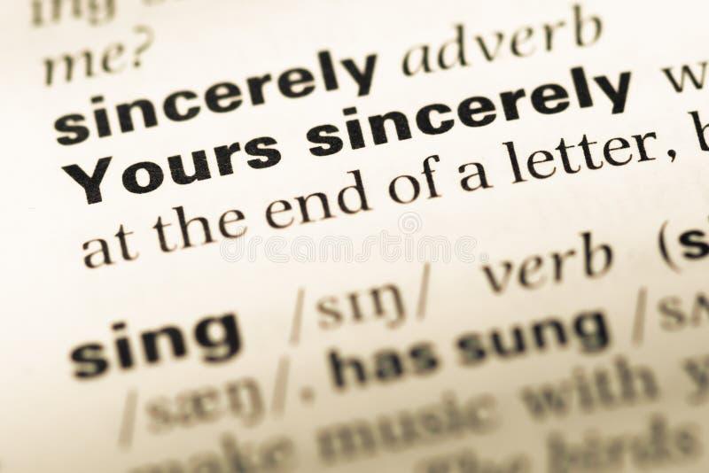 Cierre para arriba de la vieja página inglesa del diccionario con palabra sinceramente suyo imagen de archivo