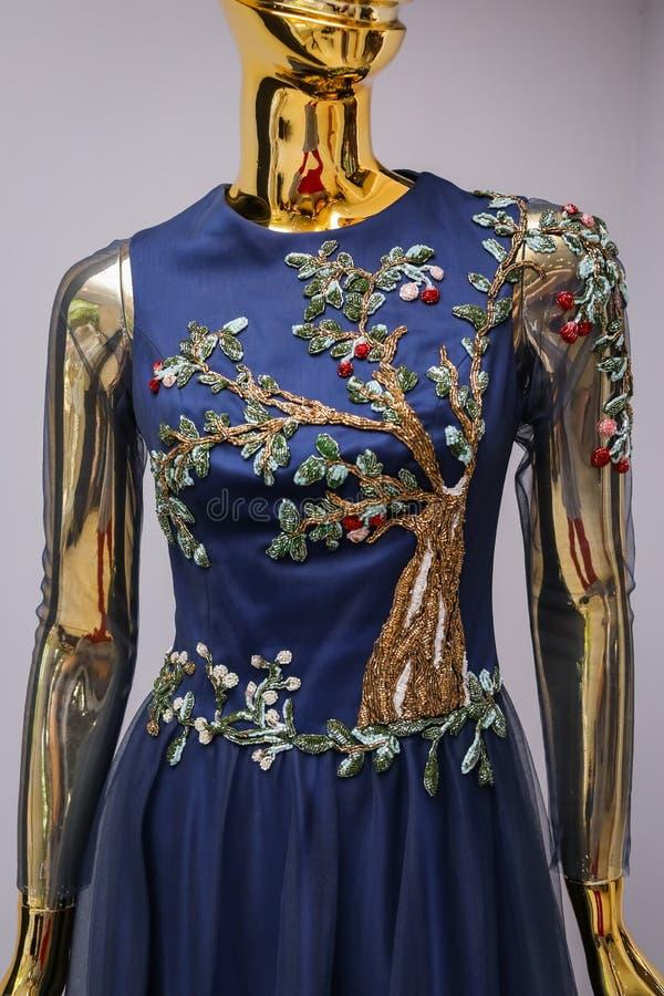 Cierre para arriba De largo, diseñador azul, tarde, el vestido de las mujeres hecho a mano en el oro, maniquí brillante Con blanc foto de archivo libre de regalías