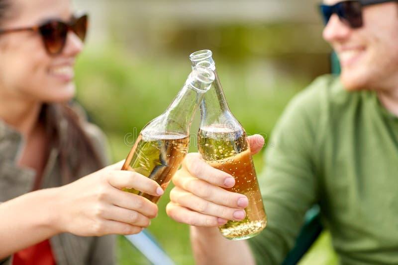 Cierre para arriba de las bebidas que tintinean de los pares felices al aire libre imagenes de archivo