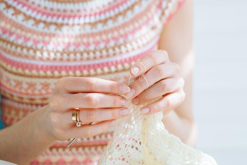 Cierre para arriba de las manos del ` s de la artesana que hacen punto el vestido con el ganchillo Trabajo femenino con el cordón imágenes de archivo libres de regalías