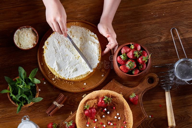 Cierre para arriba de las manos del ` s de la muchacha que añaden la crema encima de la torta deliciosa de la fresa, cierre para  foto de archivo