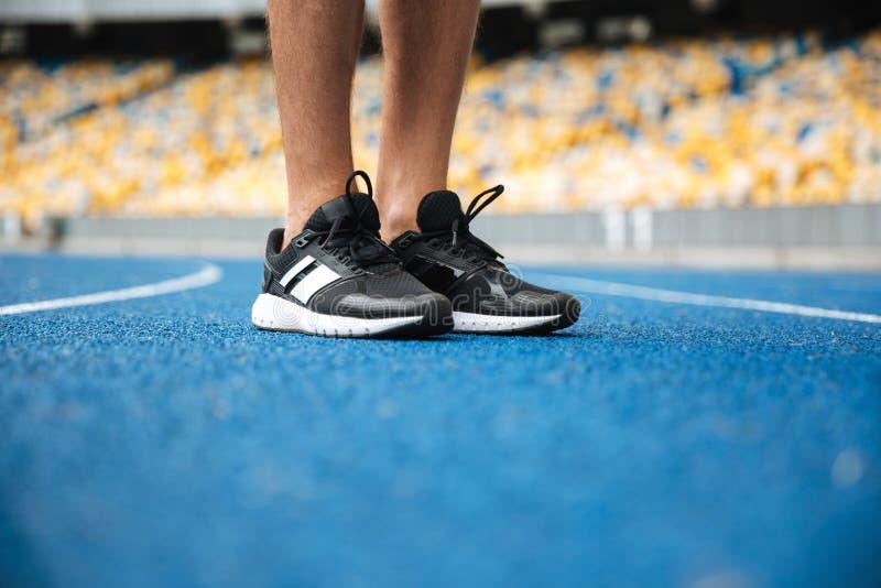 Cierre para arriba de las piernas masculinas en la colocación de las zapatillas de deporte imagen de archivo