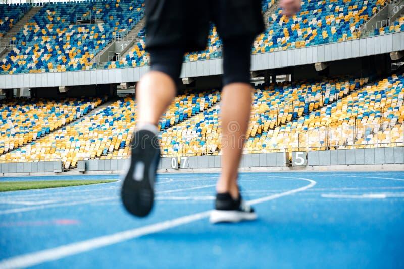 Cierre para arriba de las piernas masculinas en zapatillas de deporte en un recetrack imagenes de archivo