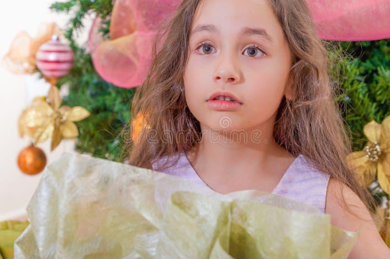 Cierre para arriba de llevar sorprendido de la muchacha los cothes rosados y de la presentación para la cámara, con un árbol de n fotos de archivo libres de regalías