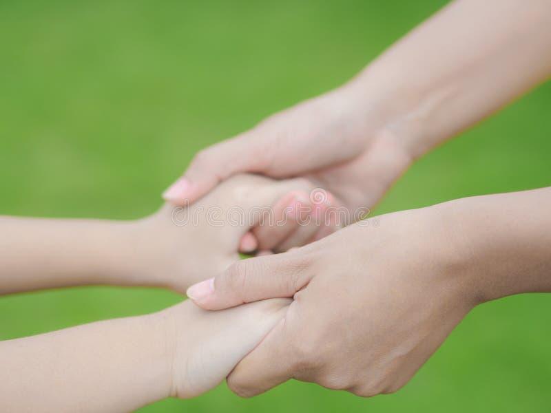 Cierre para arriba de los controles de la mujer la mano de un niño precioso fotografía de archivo libre de regalías