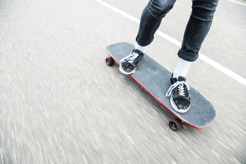 Cierre para arriba de los pies de los longboarders mientras que patina fotos de archivo