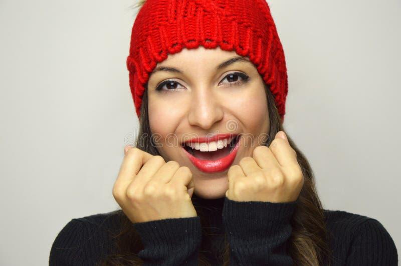Cierre para arriba de una mujer hermosa de la moda con la sonrisa roja del sombrero que mira la cámara foto de archivo
