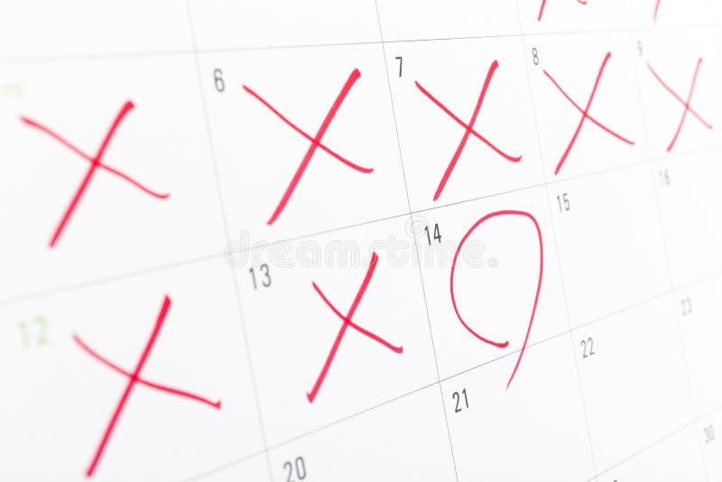 Cierre para arriba de una página blanca del calendario con alguno que los días cruzaron de X rojo fotos de archivo libres de regalías