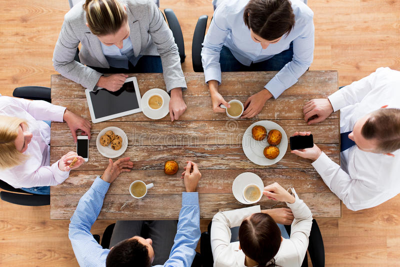 Cierre para arriba del café de consumición del equipo del negocio en almuerzo fotografía de archivo