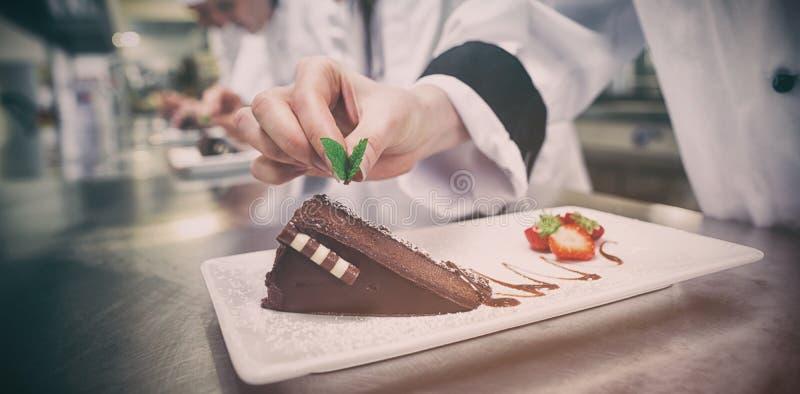 Cierre para arriba del cocinero que pone la hoja de la menta en la torta de chocolate foto de archivo