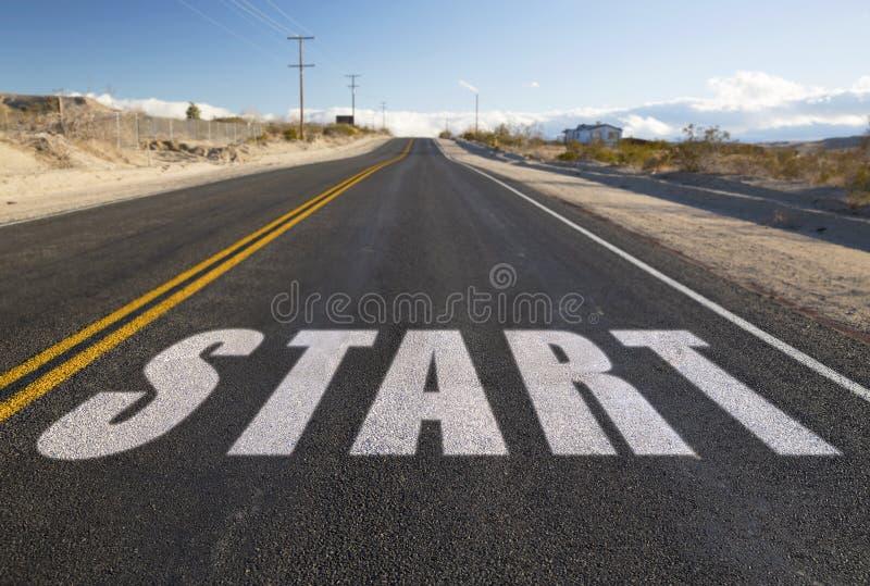 Cierre para arriba del comienzo de la palabra en la carretera de asfalto suburbana fotografía de archivo