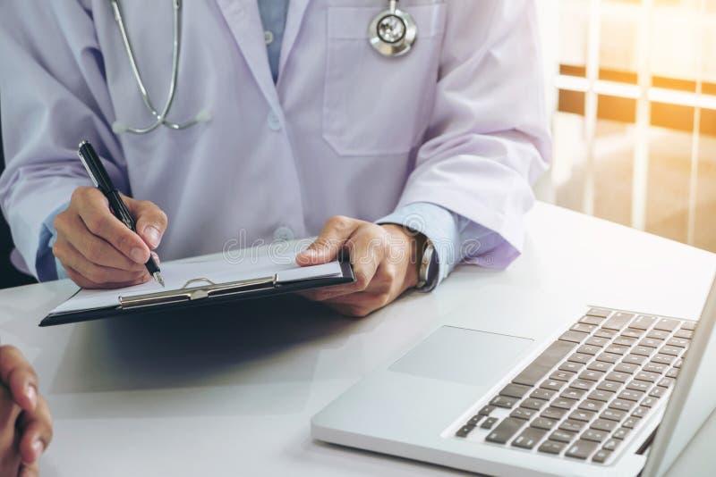 Cierre para arriba del doctor que llena encima de un formulario de la historia mientras que consulta p fotos de archivo libres de regalías