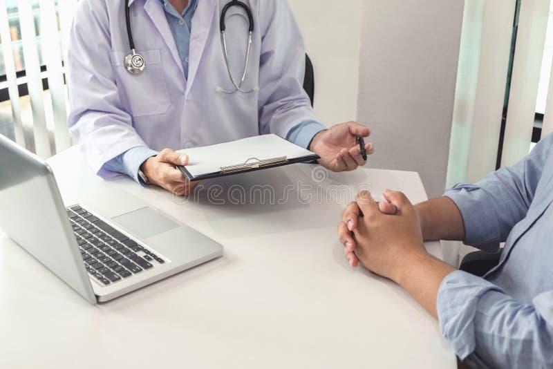 Cierre para arriba del doctor que llena encima de un formulario de la historia mientras que consulta p imagen de archivo