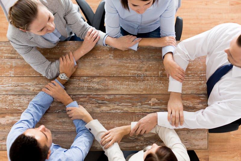 Cierre para arriba del equipo del negocio que lleva a cabo las manos en la tabla foto de archivo libre de regalías