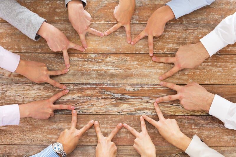 Cierre para arriba del equipo del negocio que muestra gesto de la victoria fotografía de archivo libre de regalías