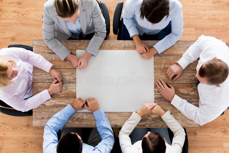 Cierre para arriba del equipo del negocio que se sienta en la tabla fotos de archivo libres de regalías