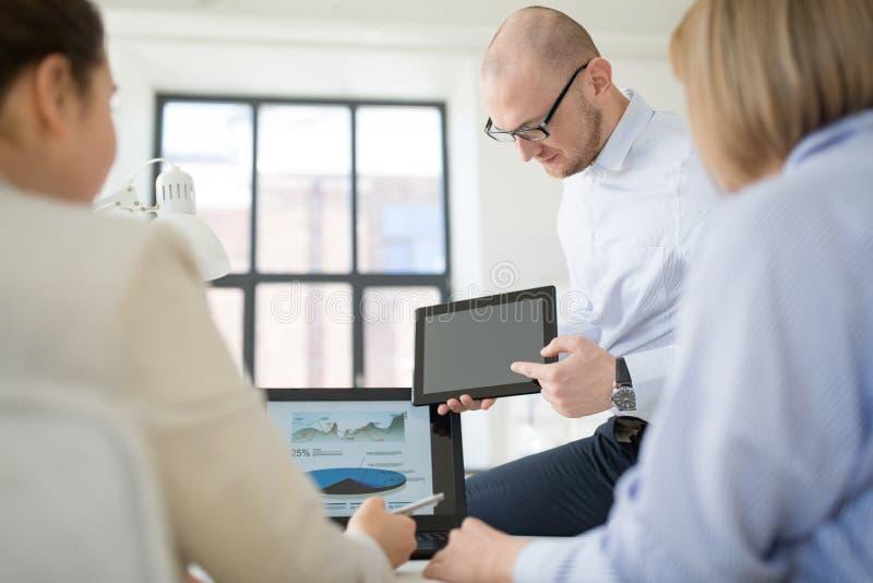 Cierre para arriba del equipo del negocio con PC de la tableta en la oficina fotografía de archivo